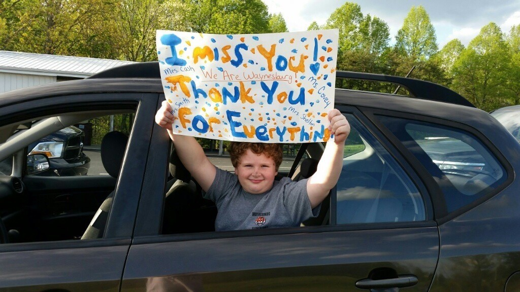 "Student holding sign saying ""I miss you!  Thank you for everything!"""